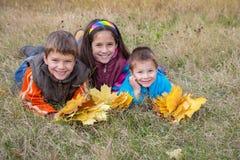Tre bambini con le foglie di autunno in parco Immagini Stock