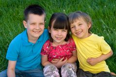 Tre bambini felici in erba Fotografie Stock Libere da Diritti