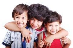 Tre bambini felici hanno isolato: amore, cura, abbraccio, Fotografie Stock