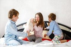 Tre bambini felici in pigiami che celebrano pigiama party Scuola materna e ragazzi e ragazza di scuola divertendosi insieme Fotografia Stock