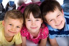 Tre bambini felici sul pavimento Fotografie Stock Libere da Diritti