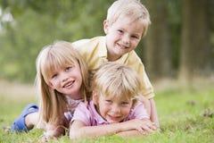 Tre bambini in giovane età che giocano all'aperto sorridere Fotografie Stock