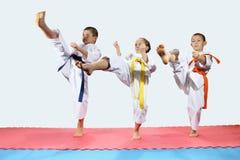 Tre bambini in karategi stanno battendo la gamba di scossa in avanti Immagini Stock Libere da Diritti