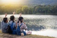 Tre bambini mangiano il ghiaccio sulla riva del fiume fotografia stock libera da diritti