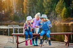 Tre bambini piccoli si vantano circa il pesce hanno preso l'esca Concetto di amicizia e fine settimana o vacanza di divertimento immagini stock libere da diritti
