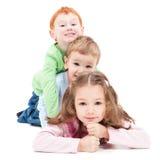 Tre bambini sorridenti che si trovano in cima a vicenda Fotografia Stock Libera da Diritti