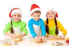 Tre bambini sorridenti con la cottura di natale fotografia stock