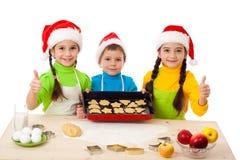 Tre bambini sorridenti con la cottura di natale Immagine Stock