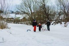 Tre bambini stanno trascinando la slitta nella montagna fotografia stock libera da diritti