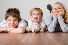 Tre bambini sul pavimento Immagini Stock Libere da Diritti