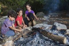 Tre bambini in un fuoco di accampamento immagini stock libere da diritti