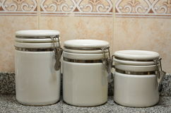 Tre barattoli ceramici bianchi sul contatore di cucina Fotografie Stock Libere da Diritti