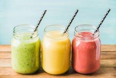 Tre barattoli dei frullati della frutta fresca con i vari colori e gusti Verde, giallo, rosso Fotografia Stock