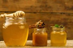 Tre barattoli di miele con drizzler, cannella, fiori su fondo di legno Immagine Stock