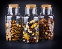 Tre barattoli di vetro con le mandorle, nocciole e frutta & dadi si mescolano Fotografia Stock