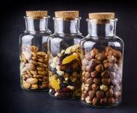 Tre barattoli di vetro con le mandorle, nocciole e frutta & dadi si mescolano Fotografie Stock