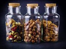 Tre barattoli di vetro con le mandorle, nocciole e frutta & dadi si mescolano Immagini Stock Libere da Diritti