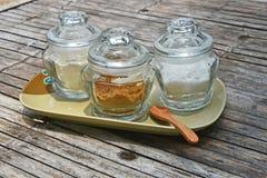 Tre barattoli di vetro di zucchero sulla tavola di bambù immagine stock