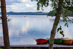 Tre barche di fila Colourful sul lago fra gli alberi Immagine Stock Libera da Diritti