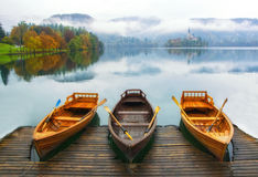 Tre barche hanno attraccato sul lago Bled al giorno nebbioso di autunno Fotografie Stock