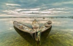 Tre barche insieme per accogliere favorevolmente il nuovo giorno hanno riflesso il lago tranquillo Immagine Stock