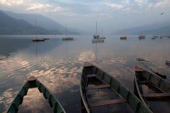 Tre barche sul lago Feva: nella priorità alta dell'alimento della barca, sommersa da acqua, nella distanza molta piccola barca, d Immagini Stock