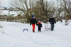 Tre barn släpar släden i berget royaltyfria foton