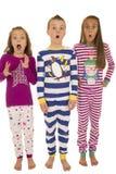 Tre barn som bär vinterpyjamas med en skrämd ansiktsbehandling exp Arkivfoton