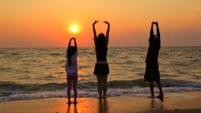 Tre barn som gör yoga, övar på stranden stock video