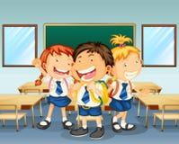 Tre barn som ler inom klassrumet Arkivbild