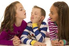Tre barn som spelar att lägga ner med enfaldiga uttryck royaltyfri foto