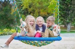 Tre barn som spelar i parkera Arkivfoton