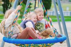 Tre barn som spelar i parkera Royaltyfri Bild