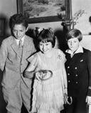 Tre barn som står spela tillsammans en lek (alla visade personer inte är längre uppehälle, och inget gods finns Leverantörwarran Royaltyfria Bilder