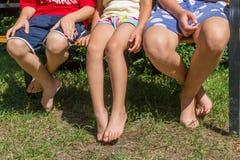 Tre barn som tillsammans sitter på bänk royaltyfri fotografi