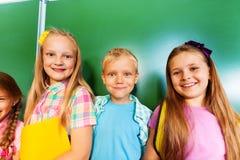 Tre barn står tillsammans nära svart tavla Arkivbild
