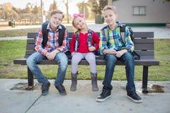 Tre barnskolaungar som sitter på en bänk Royaltyfri Fotografi