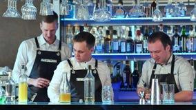 Tre bartendrar som tjänar som coctailar och arbete i en flott stång Fotografering för Bildbyråer