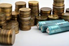 Tre batterie AAA con le monete isolate su bianco Immagini Stock Libere da Diritti
