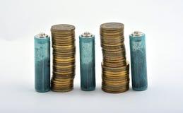 Tre batterie AAA con le monete isolate su bianco Fotografia Stock