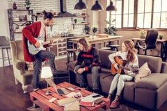 Tre begåvade musiker som har den lilla musikmusikbandet som har repetition arkivbilder