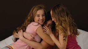 Tre bei amici che abbracciano, mentre sedendosi sul letto ed avendo pigiama party stock footage