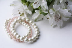 Tre bei braccialetti rosa e bianchi e fiori bianchi Immagine Stock Libera da Diritti