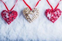 Tre bei cuori d'annata romantici stanno appendendo su una banda rossa su un fondo bianco della neve Amore e concetto di giorno di Immagini Stock