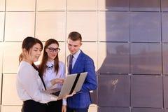 Tre bei giovani, gli studenti, due ragazze ed il ragazzo tengono la i Immagini Stock