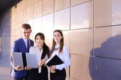 Tre bei giovani, gli studenti, due ragazze ed il ragazzo tengono la i Fotografie Stock