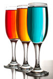 Tre bei vetri di champagne con i liquidi colorati Fotografie Stock