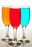 Tre bei vetri di champagne con i liquidi colorati Fotografia Stock