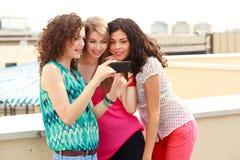 Tre belle donne che osservano su uno smartphone Fotografie Stock Libere da Diritti