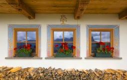 Tre belle finestre in piccola casa di campagna alpina Fotografie Stock